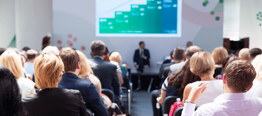Image of a conference hall audience watching a presenter