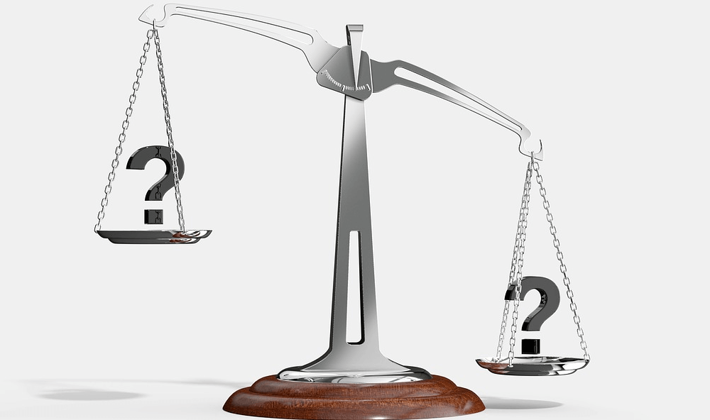Picture of a weighing scale with question-marks on each side, representing a hiring decision.