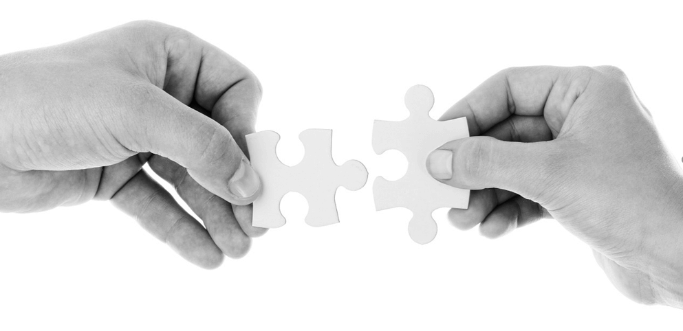 Image of two hands bringing puzzle pieces together to represent integrating WordPress and Magento